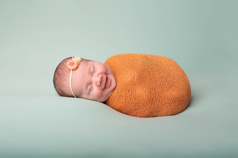 Portrait of a newborn rolled up laughing