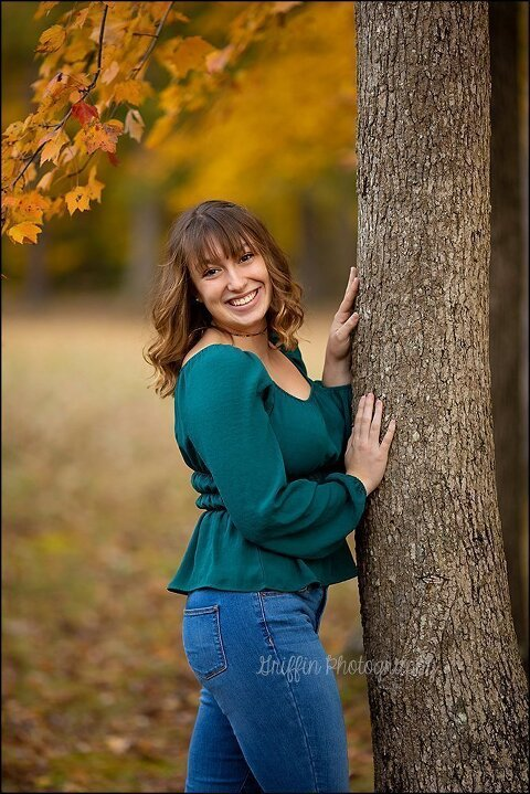 high school senior portrait smiling against tree