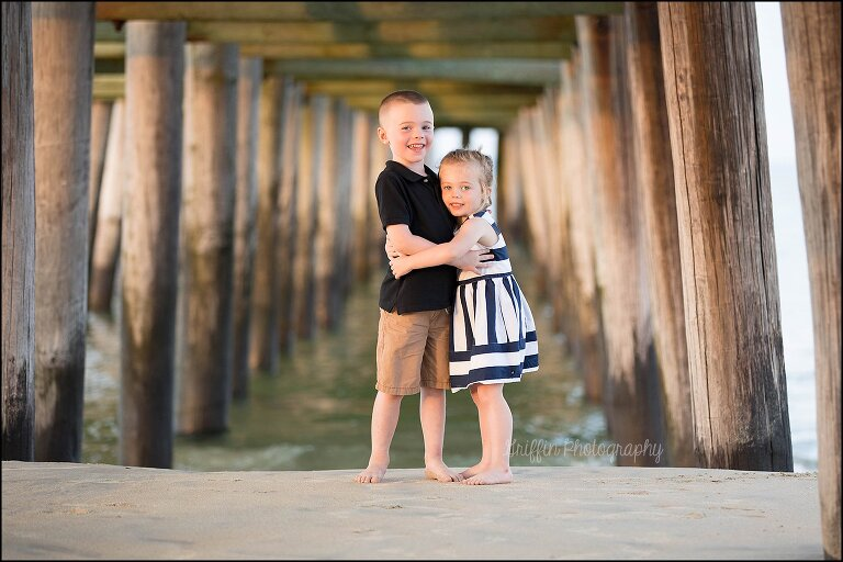 brother and sister hugging under a pier