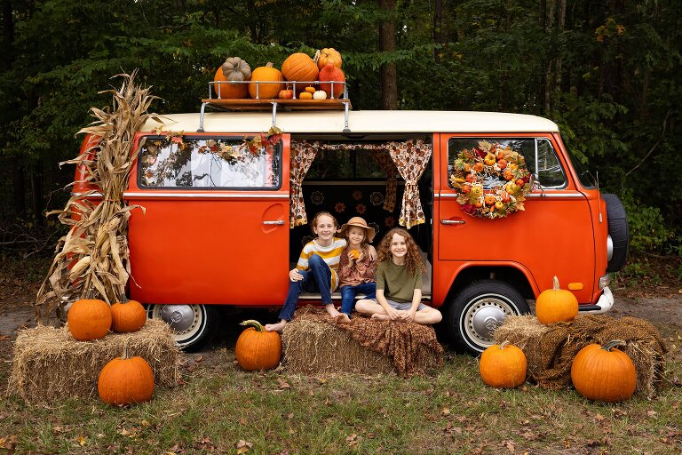 three kids on hay bales in front of orange vintage vw bus with pumpkins and autumn decorations